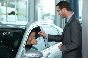 Salesman handing car keys to a new buyer